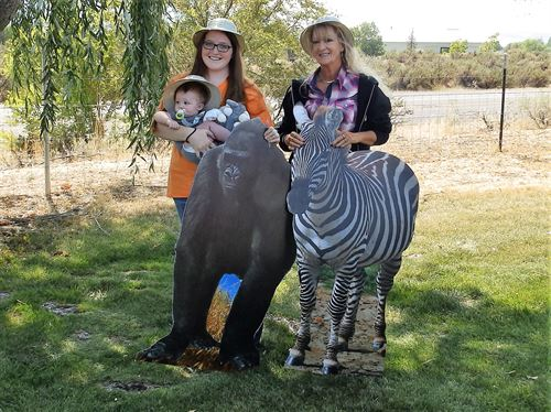 2 women and a baby, standing behind a cutout of a gorilla and a zebra